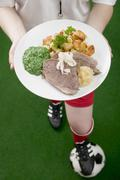 Footballer holding plate of boiled beef with accompaniments Stock Photos