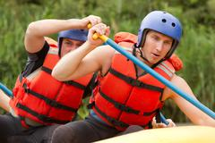 Group Of Young Athletes Training For Whitewater Rafting - stock photo