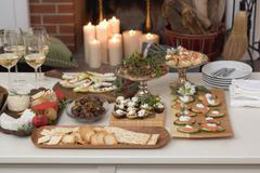 Assorted appetisers on table in front of fireplace (Christmas) Stock Photos