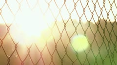 Sunset flare through chain link fence - stock footage