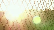 Sunset flare through chain link fence Stock Footage