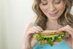 Woman holding wholemeal avocado and watercress sandwich Stock Photos