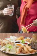 Two women with Asian appetiser platter - stock photo