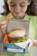 Girl holding lunch box containing burger & carrots Stock Photos