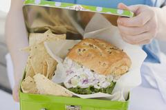 Woman holding lunch box containing chicken sandwich & crisps Stock Photos