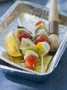 Vegetable kebabs in aluminium dish with oil and brush Stock Photos