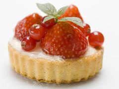 Individual strawberry and redcurrant flan with mint leaves - stock photo