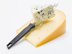 Pieces of Gouda and Gorgonzola with cheese knife Stock Photos