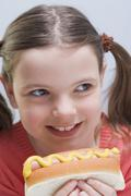Smiling girl holding hot dog with mustard - stock photo
