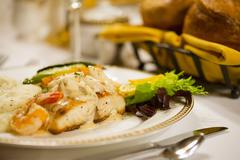 Rockfish with Crab Meat Sauce Entree on Restaurant Table Stock Photos
