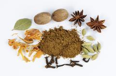 Garam masala, surrounded by cardamom, cloves, nutmeg, star anise - stock photo