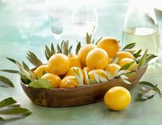 Stock Photo of Lemons with leaves in a wooden dish