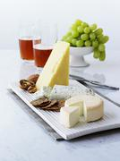 Various cheeses with crackers, walnuts, grapes, beer Stock Photos