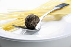 Black truffle (Chinese truffle) on fork & spaghetti on plate - stock photo