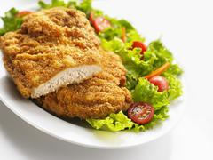 Breaded chicken breast with salad - stock photo