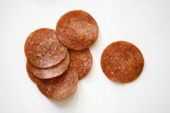 Pepperoni Slices on White Background Stock Photos