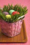 Pink Easter Basket Filled with Grass and Colored Easter Eggs Stock Photos