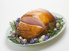 Stock Photo of Glazed roast ham surrounded by herbs, for Easter
