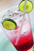 A glass of raspberry soda with ice cubes and lime slices Stock Photos