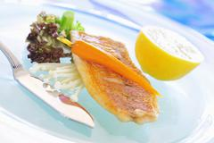 Stock Photo of Fried red snapper with carrot and enoki mushrooms