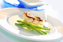 Red snapper with green asparagus on tagliatelle Stock Photos