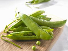 Pea pods and individual peas on chopping board - stock photo