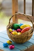 Chocolate Easter eggs in coloured foil in basket Stock Photos