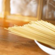 Uncooked spaghetti in a deep plate Stock Photos