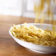 Farfalle falling onto a deep plate - stock photo