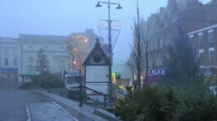 Christmas fairground rides in town centre outside shops in fog Stock Footage
