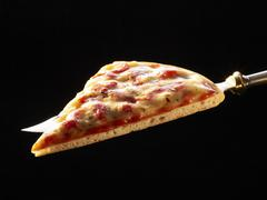 Slice of pizza on a knife Stock Photos
