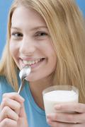 Stock Photo of Young woman eating natural yoghurt