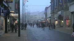 Busy pedestrianised high street at Christmas illuminated windows of shops Stock Footage