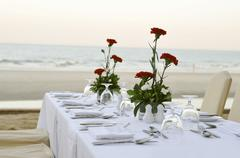 Laid table with red carnations on beach Stock Photos