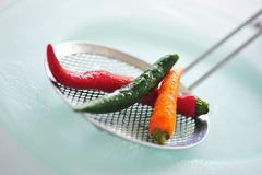 Mixed Thai chillies on a skimmer Stock Photos