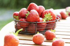 Fresh strawberries in wire basket on wooden table - stock photo