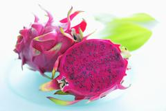 Pink-fleshed dragon fruit, whole fruit and a half - stock photo