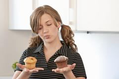 Young woman holding a muffin in each hand Stock Photos