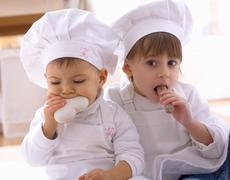 Two girls in chefs' hats eating biscuits Stock Photos