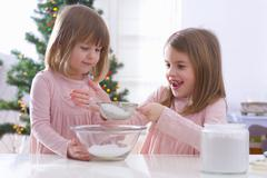 Christmas baking: two girls sieving icing sugar Stock Photos