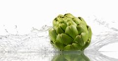 Artichoke with splashing water Stock Photos