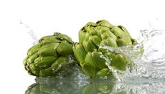 Two artichokes with splashing water - stock photo