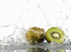 Whole and half kiwi fruit with splashing water - stock photo
