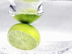 Whole Lime Dropping into Water - stock photo