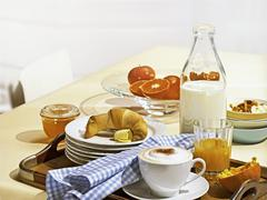 A breakfast tray with cappuccino, croissant and orange juice Stock Photos