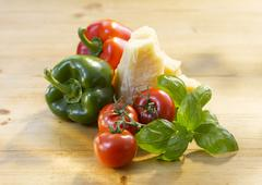 Tomatoes, peppers, basil and Parmesan cheese Stock Photos