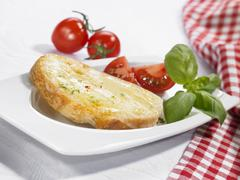Stock Photo of Cheese on toast with tomatoes and basil