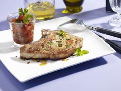 A pork chop with a glass of tomato salsa - stock photo