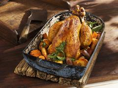Roast chicken with root vegetables in an old roasting pan - stock photo