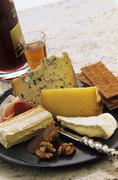 Cheese platter with nuts, crispbread, raw ham and wine - stock photo